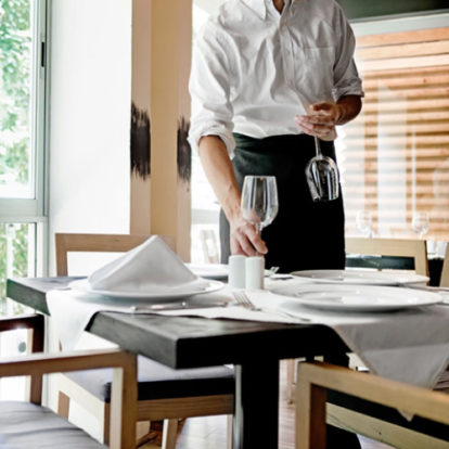 Server placing wine glasses on the restaurant table